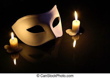Mask And Candles - White mask between lighting candles on...