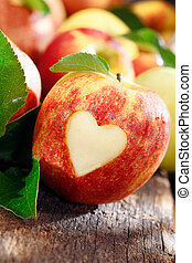 Love of apples concept with a neatly incised heart in the...