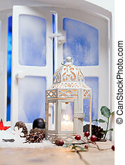 Pretty white Christmas lantern with a burning candle on a...