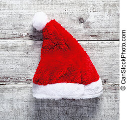 Red Santa Claus hat lying on rustic weathered wooden boards...