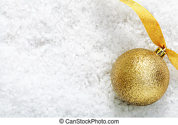 Gold glitter bauble on snow - Shiny gold glitter bauble with...