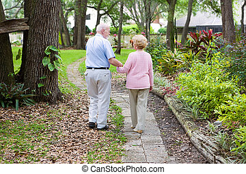 Walking Together - Senior husband and wife holding hands and...