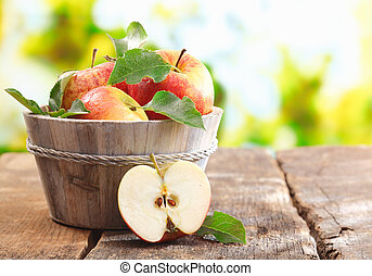 Wooden tub full and a halved fresh apple - Wooden tub full...