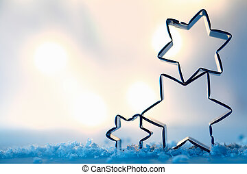 Star cookie cutters on snow crystals - Three festive star...