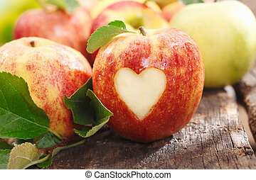 Fresh red apple with heart cutout - Fresh red apple on an...