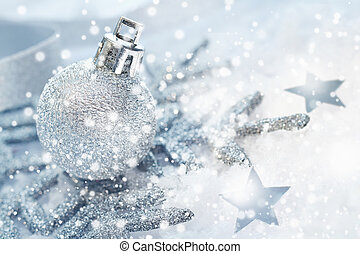 Cold wintery Christmas background with a silver bauble,...