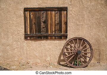 old wooden plate and wheel beside wall