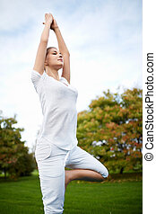 Gymnastics - Young girl doing yoga in the park