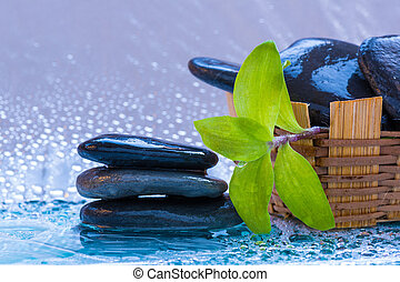 spa stones and bamboo vase on wet surfaces