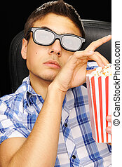 Movie critique - Young man watching movie in 3D glasses at...