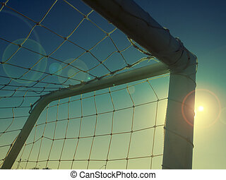 Football goal net shot into the sun with flares