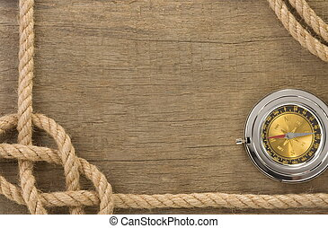 ship ropes and compass with pen on old vintage wooden