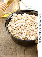 bowl of oatmeal and milk on wood background
