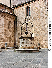 antique water well in the pictoresque nook of italian old...