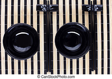 classical asian chopsticks and black bowls for two persons...