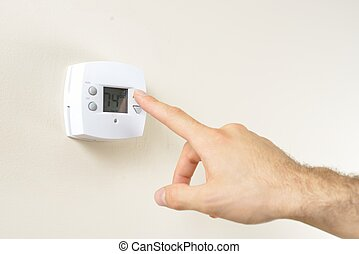 Hand Changing Thermostat - Hand changing temperature on a...