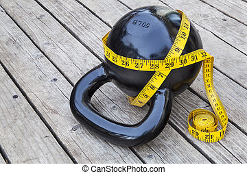 kettlebell and measuring tape on wooden deck - fitness and...