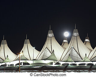 Denver International Airport at dusk with full moon.