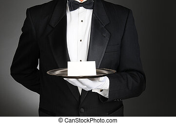 Butler With Note on Tray - A butler wearing a tuxedo holding...