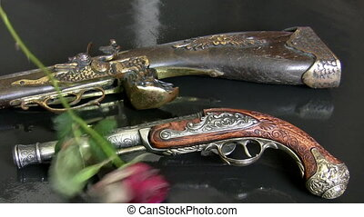 Antique guns and withered roses