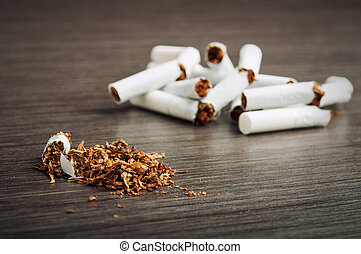heap of broken cigarettes and tobacco on a dark wooden...