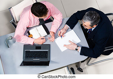 Communication - View from above of two businessmen speaking...
