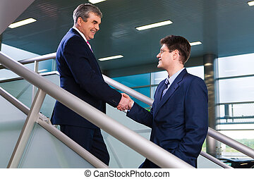 Greeting - Photo of two business partners greeting each...