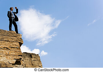 Observer - Image of elegant man standing on the cliff with...