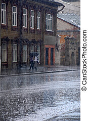 Walking in the Rain - Two women walk in the rain down the...