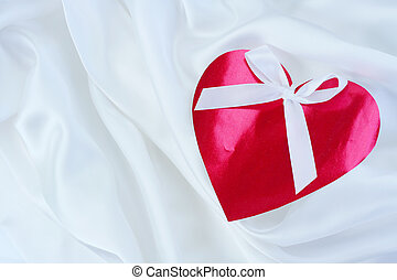 Red heart with ribbon on white satin