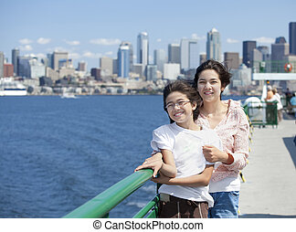Two sisters on ferry deck with Seattle skyline in background...