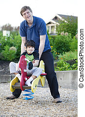 Father helping disabled son play at - Father helping...