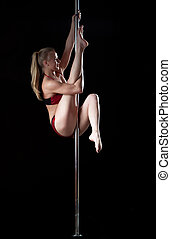 Blond woman prepare for split during pole dance