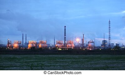Phosphoric factory in light of lanterns stand against evening sky