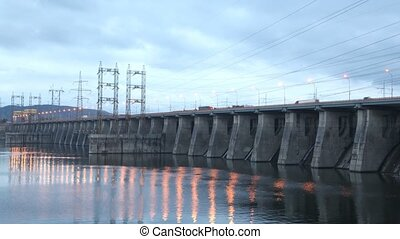 Cars go on bridge in night which is also spillway dike, time...