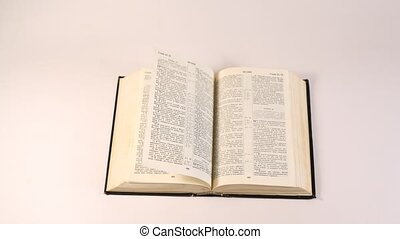 Bible lies on white table, pages are looked through by wind...
