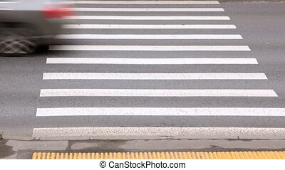 Cars quickly go on pedestrian crossing near sidewalk, time...