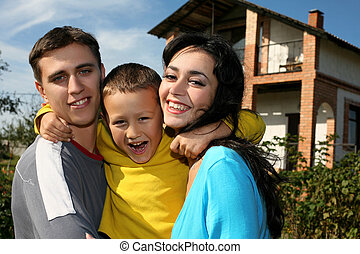 Young happy family beside their new house