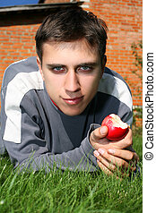 man in green grass with apple