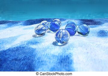 Marbles - Blue marbles on a towel by the swimming pool