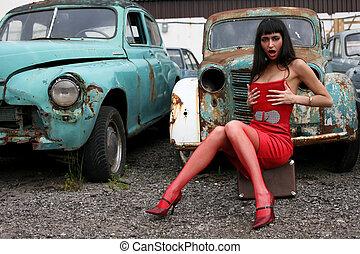 girl sit atop vintage suitcase beside retro cars