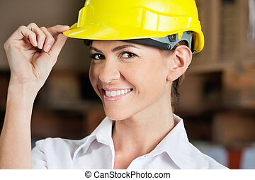 Female Supervisor Touching Hardhat At Warehouse - Portrait...