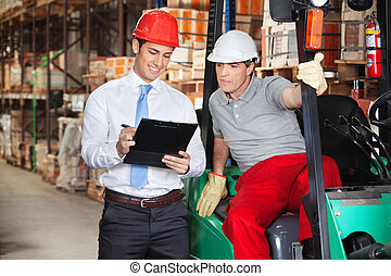 Supervisor Showing Clipboard To Foreman - Young supervisor...