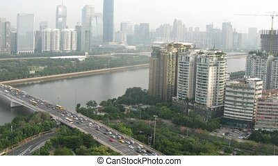Zhujiang New Town stands on opposite to river behind bridge,...