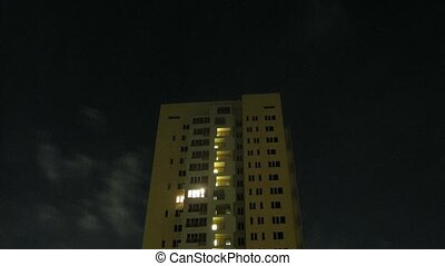 Light shine in windows of high-rise building at night, time...