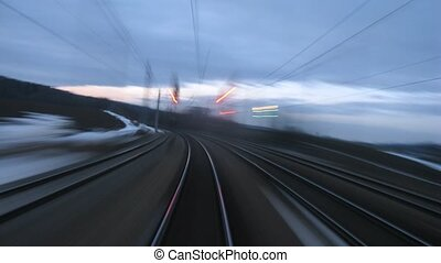 Train goes by rail near with inhabited locality along...