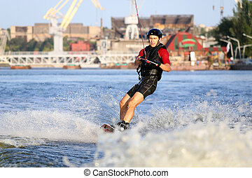 Wakeboarder surfing across a river - Wakeboarder surfing...