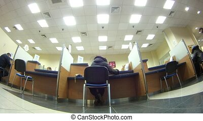 Client sit on chair and makes transaction in bank, time...