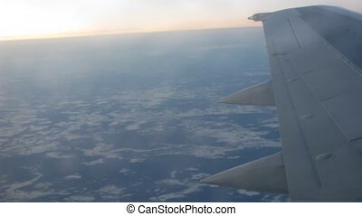 From window of flying plane is visible sunset and Earth