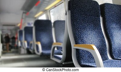 Dark blue chairs with yellow armrests stand in carriage of train, time lapse